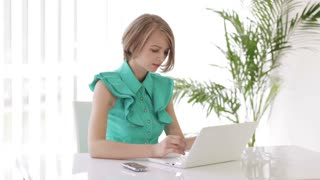 Pretty young woman sitting at desk using laptop looking at camera and smiling. Panning camera