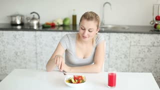 Pretty young woman sitting at kitchen table eating vegetable salad and smiling