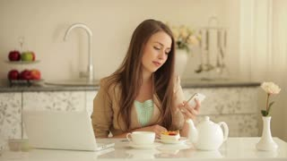 Pretty young woman sitting at kitchen table using mobile phone pouring tea into cup and smiling
