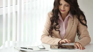 Pretty young woman sitting at office table using touchpad and smiling