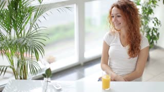 Pretty young woman sitting at table drinking juice and smiling at camera