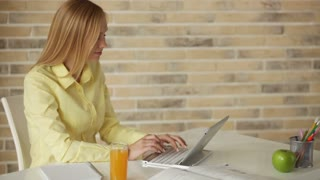 Pretty young woman sitting at table drinking juice using laptop looking at camera and smiling. Panning camera