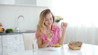 Pretty young woman sitting in kitchen eating salad with bread and smiling