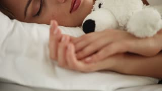 Pretty young woman sleeping in bed hugging teddy bear and smiling in her sleep. Panning camera