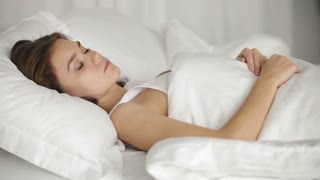 Pretty young woman sleeping in bed turning around and smiling in her sleep. Panning camera
