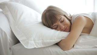 Pretty young woman sleeping in bed waking up and looking at camera with smile