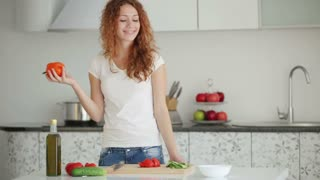 Pretty young woman standing in kitchen cutting vegetables and smiling at camera