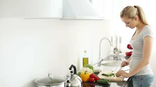 Pretty young woman standing in kitchen cutting vegetables turning around and smiling at camera