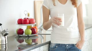 Pretty young woman standing in kitchen drinking milk from glass and smiling at camera