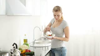 Pretty young woman standing in kitchen eating vegetable salad and smiling at camera