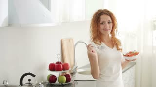 Pretty young woman standing in kitchen eating vegetable salad from bowl and smiling