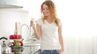 Pretty young woman standing in kitchen holding glass of milk and smiling at camera