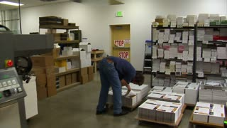 Printing Press Operator Sorts Through Finished Materials On Pallets