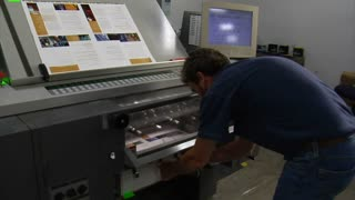 Printing Press Technician Examines Final Product