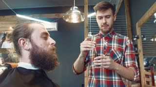 Professional barber smearing oil over client's beard