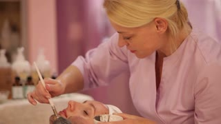 Professional beautician applying cosmetic mask on female face at beauty salon. Panning camera