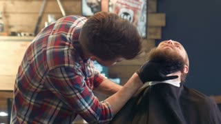Professional haircutter touching man's thick beard in black gloves