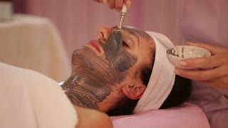 Professional massage therapist applying cosmetic mask on female face. Panning camera