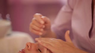 Professional massage therapist doing massage of female face at beauty spa. Panning camera
