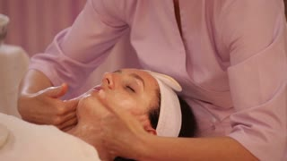 Professional massage therapist massaging female face at beauty salon. Panning camera