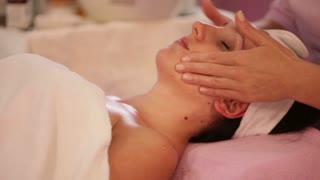 Professional massage therapist massaging woman's face at beauty spa. Panning camera