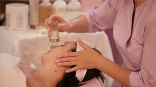 Professional massage therapist preparing female face for massage. Panning camera