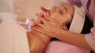 Professional masseuse doing massage of female face at beauty spa