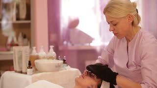 Professional masseuse massaging female face with gloves at beauty spa. Panning camera