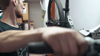 Professional mechanic checking and repairing bike in workshop