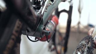 Professional mechanic repairing bike wheel with tool in workshop