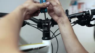 Professional mechanic repairing bike with tools in workshop