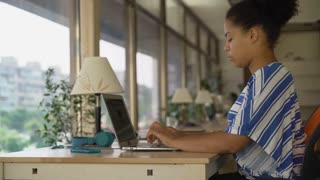 Professional woman works near big panoramic office. Mixed race female typing on the laptop sitting at the working place. Girl wearing in casual dress with blue strips