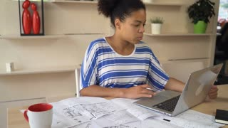 Professional young designer checking plan with electronical version on computer. African mixed race female looking on screen laptop and test plan of new building. Black girl doing her work