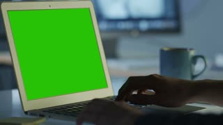 Programmer is Working in Office on Laptop with Green Screen for Mock-up