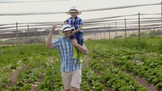 Proud farming father showing son the fields on their farm.