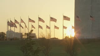 punch-in sun setting behind waving flags, George Washington monument