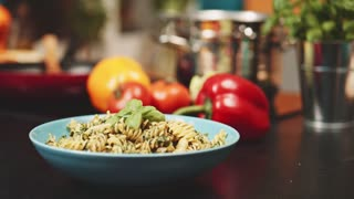 Putting parmesan cheese on pasta, Slow Motion 120 fps, dolly shot. Woman hands covering fusilli pasta with Italian cheese at the kitchen background. Delicious food, home cooking, healthy eating. 4K