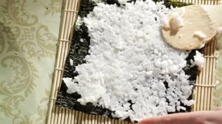Putting rice on nori. Making sushi rolls. High angle view.