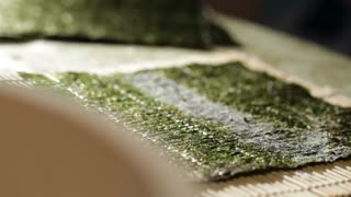 Putting rice on nori. Making sushi rolls.