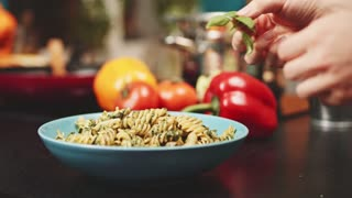 Putting sweet basil leaf on pasta, Slow Motion 120 fps, dolly shot. Woman hands decorating hot fusilli pasta with green basil leaf at the kitchen background. Delicious food, home cooking. 4K
