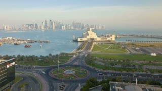Qatar, Middle East, Arabian Peninsula, Doha, Elevated view over the Museum of Islamic Art and the Dhow harbour to the modern skyscrapper skyline, T/Lapse