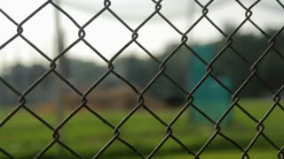 Rack focus of a fence to an empty batting cage.