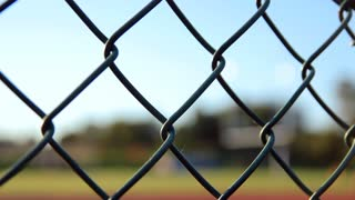 Rack focus of fence to goal post in football stadium.