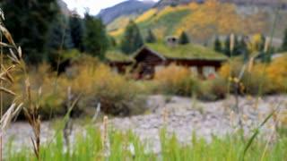 Rack focus onto a cozy cabin in the Colorado Rocky Mountains in autumn
