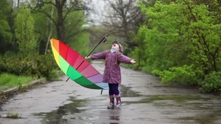 Rain. Happy little girl with an umbrella in hand catches raindrops mouth and laughs