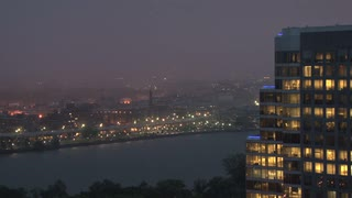 Rainy Evening Over River and City Buildings