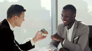 Real-estate black agent with man signing contract in modern white european office