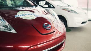 Red electric car closeup on the cap and charging point on the front hood in a concept of eco friendly transport