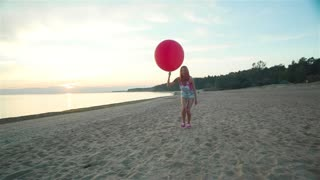 Red haired girl with closed eyes lets go a big red balloon on the beach