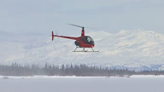 Red Helicopter Hovering Over Snowy Ground